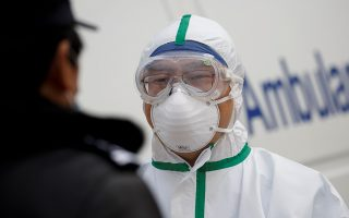 A hospital staff member in protective garments talks to a police officer at a checkpoint to the Hubei province exclusion zone at the Jiujiang Yangtze River Bridge in Jiujiang, Jiangxi province, China, as the country is hit by an outbreak of a new coronavirus, February 1, 2020.  REUTERS/Thomas Peter