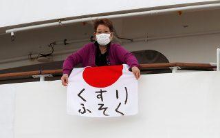 Μια γυναίκα κρεμάει μία ιαπωνική σημαία με τις λέξεις «έλλειψη φαρμάκων» στο κρουαζιερόπλοιο που βρίσκεται σε καραντίνα από τις 3 Φεβρουαρίου