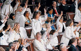 Ντυμένες στα λευκά, γυναίκες-μέλη του Κογκρέσου υψώνουν συμβολικά τρία δάχτυλα σε ένδειξη υποστήριξης προς τη μεταρρύθμιση Ομπάμα στην υγεία.