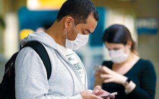 Aπαραίτητα εφόδια όχι μόνο τα κινητά, που διευκολύνουν τη διαρκή ενημέρωση, αλλά και οι χειρουργικές μάσκες στη Βραζιλία, η οποία πρόσφατα ανακοίνωσε το πρώτο κρούσμα COVID-19.