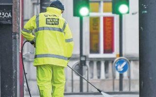 Οδοκαθαριστής πλένει το πεζοδρόμιο όπου σημειώθηκε η επίθεση την Κυριακή, στο νότιο Λονδίνο.