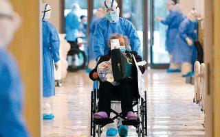 Νοσηλευτής μεταφέρει ασθενή σε νοσοκομείο της πόλης Γουχάν στις 10 Φεβρουαρίου. Στην επαρχία Χουμπέι, με πρωτεύουσα τη Γουχάν, έχει σημειωθεί σχεδόν το σύνολο των θανάτων από τον ιό COVID-19.