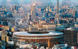 Πρόσωπα καλυμμένα με μάσκες λόγω του κορωνοϊού αντανακλώνται σε τζάμι κτιρίου του Τόκιο με φόντο το Ολυμπιακό Στάδιο της πόλης, την οποία έχει χτυπήσει ο κορωνοϊός και οδεύει προς τους 32ους Ολυμπιακούς Αγώνες.