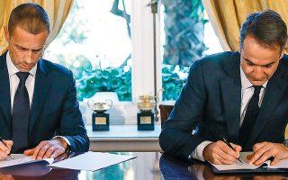 Ο πρωθυπουργός Κυριάκος Μητσοτάκης υπογράφει το συνυποσχετικό με τον πρόεδρο της UEFA Aλεξάντερ Τσέφεριν, χθες, στο Μέγαρο Μαξίμου για τη βελτίωση και την αναβάθμιση του ελληνικού ποδοσφαίρου.