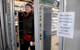 epa08249762 A person walks out of a pharmacy which has fixed a note on the front door informing of the running out of stocks of protective masks and disinfectant products in Milan, Italy, 26 February 2020. Civil Protection Chief Angelo Borrelli said that the number of people which have died due to the COVID-19 coronavirus in Italy has climbed to 12 while 374 have contracted the virus.  EPA/OURAD BALTI TOUATI