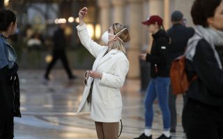 A woman wearing sanitary mask takes a selfie in downtown Milan, Italy, Sunday, Feb. 23, 2020. In Lombardy, the hardest-hit region with 90 cases Coronavirus infections, schools and universities were ordered to stay closed in the coming days, and sporting events were canceled.  (AP Photo/Antonio Calanni)
