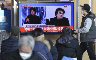 People watch a TV screen showing images of South Korean director Bong Joon Ho during a news program at the Seoul Railway Station in Seoul, South Korea, Monday, Feb. 10, 2020. In a milestone win that instantly expanded the Oscars' horizons, Bong's masterfully devious class satire