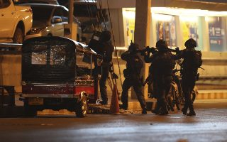 A group of armed commando soldiers are seen outside Terminal 21 Korat mall, in Nakhon Ratchasima, Thailand on Sunday, Feb. 9, 2020.A soldier who holed up in a popular shopping mall in northeastern Thailand shot multiple people on Saturday, killing at least 20 and injuring 31 others, officials said. (AP Photo/Sakchai Lalitkanjanakul)