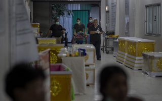 Morgue staff push a trolley carrying a victim of a mass shooting, at a morgue in Korat, Nakhon Ratchasima, Thailand, Sunday, Feb. 9, 2020. Thai officials say a soldier who went on a shooting rampage and killed numerous people and injured dozens of others has been shot dead inside the mall in northeastern Thailand. (AP Photo/Gemunu Amarasinghe)