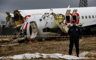 Turkish police guard the wreckage of a plane operated by Pegasus Airlines after it skidded Wednesday off the runway at Istanbul's Sabiha Gokcen Airport, in Istanbul, Thursday, Feb. 6, 2020. Flights resumed Thursday after the airliner skidded off a runway, killing three people and injuring dozens. The Boeing 737, carrying 177 passengers and six crew members, landed during strong winds and heavy rain, overshot the runway and broke up into three parts upon impact. (AP Photo/Emrah Gurel)