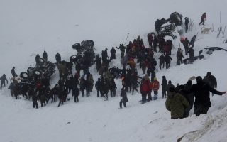 Emergency service members work in the snow around overturned vehicles, near the town of Bahcesaray, Van province, eastern Turkey, Wednesday, Feb. 5, 2020. An avalanche slammed into a mountain road in the province, which borders Iran, wiping out a huge team of rescue workers sent to find two people missing in an earlier avalanche. (Yilmaz Sonmez/IHA via AP)