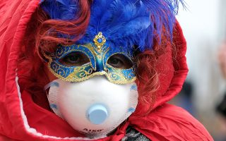 Masked carnival reveller wears protective face mask at Venice Carnival, which the last two days of, as well as Sunday night's festivities, have been cancelled because of an outbreak of coronavirus, in Venice, Italy February 23, 2020.  REUTERS/Manuel Silvestri