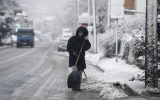 Μία γυναίκα καθαρίζει το χιόνι έξω από την κατοικία της στο χωριό του Χορτιάτη