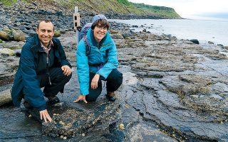 Δύο επιστήμονες του Πανεπιστημίου του Εδιμβούργου μπροστά σε ένα αποτύπωμα δεινοσαύρου, στο Isle of Skye της Σκωτίας.