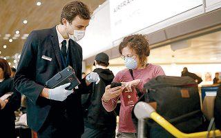Υπάλληλος της Air France βοηθάει ταξιδιώτες στο διεθνές αεροδρόμιο «Σαρλ ντε Γκωλ», στο Παρίσι. Οι απαγορεύσεις πτήσεων από αρκετές ευρωπαϊκές χώρες προκάλεσαν αναστάτωση στις μεταφορές.