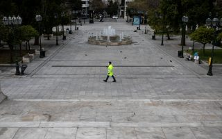 A municipal worker wearing a protective face mask walks on the empty Syntagma square, after the Greek government imposed a nationwide lockdown to contain the spread of the coronavirus disease (COVID-19), in Athens, Greece, March 23, 2020. REUTERS/Alkis Konstantinidis