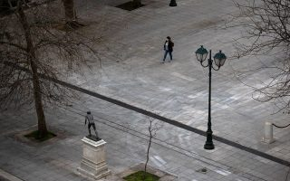 A woman wearing a protective face mask makes her way on the empty Syntagma square, after the Greek government imposed a nationwide lockdown to contain the spread of the coronavirus disease (COVID-19), in Athens, Greece, March 23, 2020. REUTERS/Alkis Konstantinidis