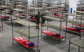 Members of the Logistics Brigade of the Spanish Army are pictured next to bunk beds for homeless people at a shelter in the Fira Pavilion, as the coronavirus disease (COVID-19) outbreak continues, in Barcelona, Spain March 25, 2020. REUTERS/Nacho Doce