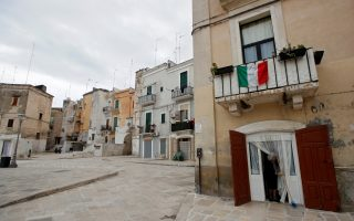 A woman sweeps the floor outside her home, during the coronavirus disease (COVID-19) outbreak in Bari, Italy, March 31, 2020. The flag reads: