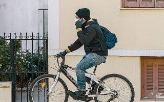 Ποδηλάτης με προστατευτική μάσκα και γάντια, ως μέτρο πρόληψης για την αποφυγή μετάδοσης του ιού.
