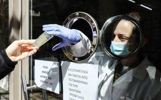 Εξυπηρέτηση πελατών σε φαρμακείο μέσα από παραθυράκι.