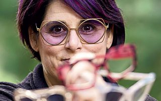 Αμερικανίδα οπτικός επιδεικνύει πολλά ζευγάρια γυαλιών, μετά το κλείσιμο του καταστήματός της στο Μπερκ της Βιρτζίνια.