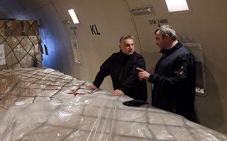 Ο Ούγγρος πρωθυπουργός Βίκτορ Ορμπαν και ο υπουργός Καινοτομίας Λάσλο Πάλκοβιτς συζητούν μπροστά από ιατρικό υλικό που έφτασε από την Κίνα.