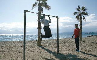 Κόσμος αθλείται στην παραλία του Αλίμου, μεμονωμένα, λόγω των αυστηρών μέτρων για τον περιορισμό της εξάπλωσης του κορωνοϊού.