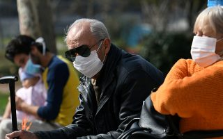 FILE PHOTO: People wearing protective face masks sit outside the AHEPA hospital, where Greece's first confirmed coronavirus case was treated, in Thessaloniki, Greece, February 26, 2020. REUTERS/Alexandros Avramidis/File Photo