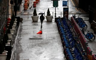 A man carries an umbrella as he walks past stalls of parked Citi Bikes in midtown Manhattan as the coronavirus disease (COVID-19) outbreak continues in New York City, New York, U.S., March 23, 2020. REUTERS/Mike Segar