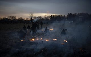 Migrants are seen through a smoke as they set a fire between the Turkish-Greek border in Pazarkule, Turkey, on Friday, March 6, 2020. Clashes erupted anew on the Greek-Turkish border as migrants attempted to push through into Greece, while the European Union's foreign ministers held an emergency meeting to discuss the situation on the border and in Syria, where Turkish troops are fighting. (AP Photo/Felipe Dana)