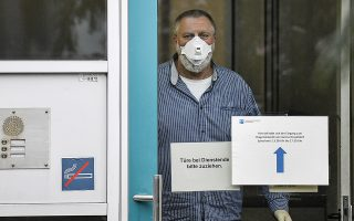 An employee with face mask and gloves waits behind the door of the corona diagnostic center in Duesseldorf, Germany, Monday, March 2, 2020 for the next patient. Germany faces several people infected with the novel coronavirus called COVID-19, most cases in North Rhine-Westphalia. (AP Photo/Martin Meissner)