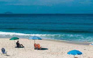 Ανδρας στη, λόγω πανδημίας, άδεια παραλία της Ιπανίμα, χθες, στο Ρίο ντε Τζανέιρο της Βραζιλίας.