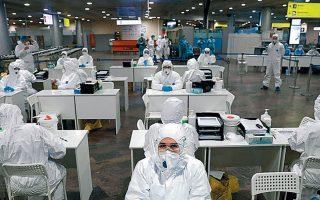 Ρώσοι ειδικοί περιμένουν να εξετάσουν ταξιδιώτες από άλλες χώρες στο αεροδρόμιο Σερεμέτιεβο της Μόσχας.