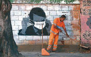 Εργάτης του δήμου καθαρίζει τον δρόμο μπροστά από γκράφιτι που εικονίζει τον πρόεδρο Μπολσονάρο, στο Ρίο.