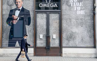 Ανδρας που φοράει μάσκα περπατάει μπροστά από μαγαζί που διαφημίζει τη νέα ταινία Τζέιμς Μποντ στο Λονδίνο.