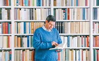 Ο Κώστας Κωστής φωτογραφημένος μπροστά από τη βιβλιοθήκη του.