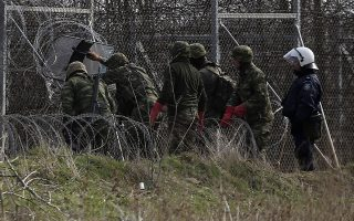 Greek soldiers fix the damages at a fence at the Kastanies border gate at the Greek-Turkish border, Monday, March 2, 2020. Thousands migrants massed at the Turkish-Greek border, and hundreds more crossed from the Turkish coast to nearby Greek islands in dinghies over the weekend, after Turkey declared its borders open amid a Russia-backed Syrian government offensive into Syria's northwestern Idlib province. (AP Photo/Giannis Papanikos)