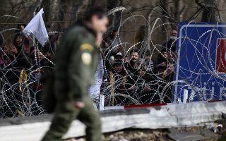 Migrants stand behind a fence near the Kastanies border gate at the Greek-Turkish border, Monday, March 2, 2020. Thousands migrants massed at the Turkish-Greek border, and hundreds more crossed from the Turkish coast to nearby Greek islands in dinghies over the weekend, after Turkey declared its borders open amid a Russia-backed Syrian government offensive into Syria's northwestern Idlib province. (AP Photo/Giannis Papanikos)