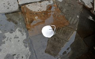 A mask is left in a puddle in Piazza del Duomo, as Italy battles a coronavirus outbreak, in Florence, Italy, March 10, 2020. REUTERS / Jennifer Lorenzini