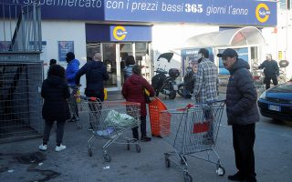 People wait in the line to buy food and goods after the Italian government locks down whole country as new coronavirus cases surge, in Naples, Italy March 10, 2020. REUTERS/Ciro De Luca