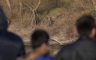 Migrants look as a Greek soldier patrols on the banks of Evros river, natural border between Turkey and Greece, pictured from Turkey's side near Edirne, Turkey, March 3, 2020. REUTERS/Marko Djurica