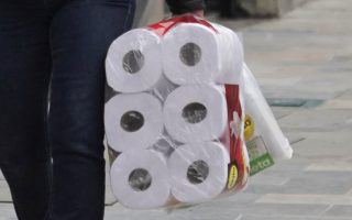 A woman walks down a street carrying a toilet paper package during the four-day mandatory isolation decreed by the mayor of Bogota, as a preventive measure against the spread of the coronavirus disease (COVID-19), in Bogota, Colombia March 20, 2020. REUTERS/Nathalia Angarita NO RESALES. NO ARCHIVES.