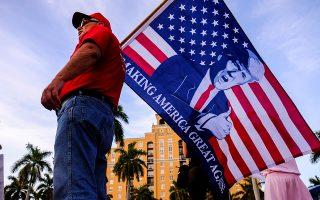 A supporter of U.S. President Donald Trump holds a flag with an image of Trump outside the convention center where Democratic U.S. presidential candidate Michael Bloomberg is holding his Super Tuesday night rally, in West Palm Beach, Florida, U.S., March 3, 2020. REUTERS/ Maria Alejandra Cardona