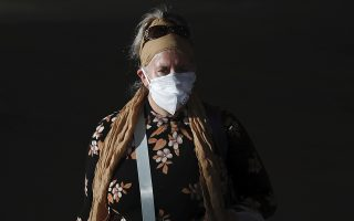 A passenger wears a mask to help protect against coronavirus, at the Ben Gurion airport near Tel Aviv, Israel, Sunday, March 8, 2020. (AP Photo/Ariel Schalit)