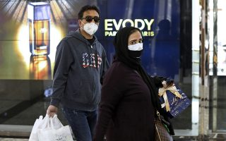 People wearing face masks and gloves shop at the Palladium Shopping Center, in northern Tehran, Iran, Tuesday, March 3, 2020. Iran's supreme leader put the Islamic Republic's armed forces on alert Tuesday to assist health officials in combating the outbreak of the new coronavirus, the deadliest outside of China. (AP Photo/Vahid Salemi)