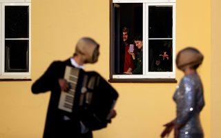 Ντε Κίρικο. Ισως να φταίει το έντονο κίτρινο χρώμα της πολυκατοικίας στην Πράγα. Ισως οι μάσκες των μουσικών που θέλησαν να διασκεδάσουν τους κλεισμένους στα διαμερίσματα για την καραντίνα.  REUTERS/David W Cerny