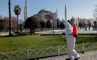 A worker in protective suit disinfects Sultanahmet square in response to the spread of coronavirus disease (COVID-19) in Istanbul,Turkey March 21, 2020. Byzantine-era monument of Hagia Sophia is seen in the background. REUTERS/Kemal Aslan