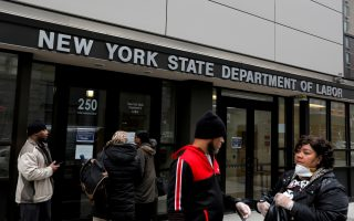 FILE PHOTO: People gather at the entrance for the New York State Department of Labor offices, which closed to the public due to the coronavirus disease (COVID-19) outbreak in the Brooklyn borough of New York City, U.S., March 20, 2020. REUTERS/Andrew Kelly/File Photo