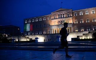 A man jogs as the Italian flag is projected on the Greek parliament building in solidarity with Italy, over the coronavirus (COVID-19) pandemic, in Athens, Greece, April 3, 2020. REUTERS/Alkis Konstantinidis